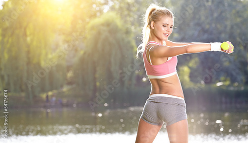Fotografie, Obraz  female fitness instructor exercising with small weights in gree