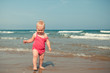 Adorable girl walking along beach