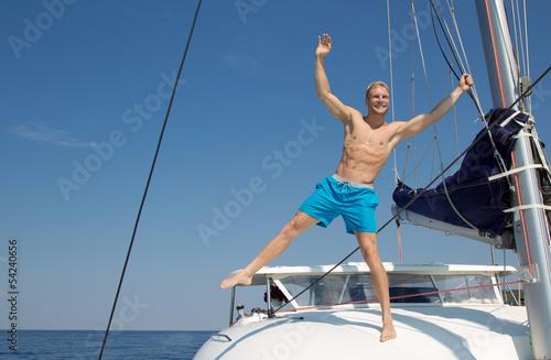 Fotomural  Grenzenlose Freiheit - Mann auf einem Katamaran am Meer