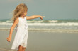 happy little girl standing on the beach and showing at the se