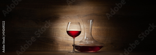 Photo decanter with red wine and glass on a wood panorama background