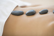 Woman Getting Hot Stone Therapy At Spa