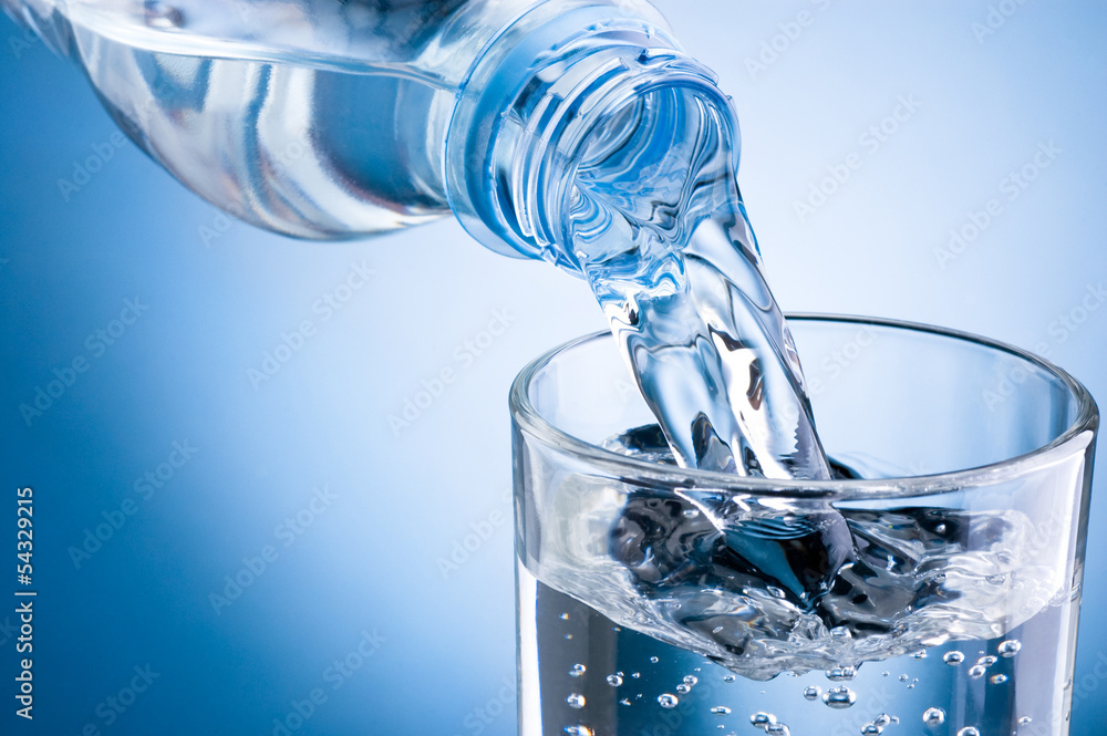 Fototapeta Pouring water from bottle into glass on blue background