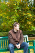 young man in the autumn park sitting on bench