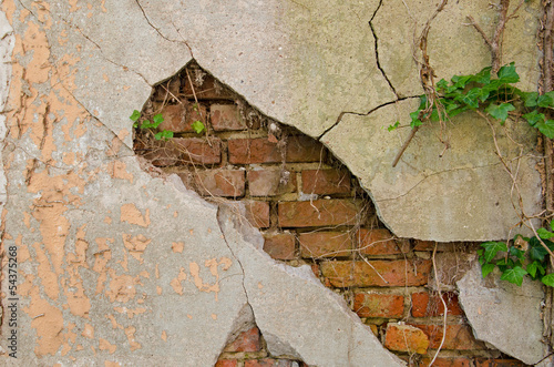 Fototapeta cegła mur-z-pekajacym-tynkiem-i-widocznymi-pod-nim-ceglami