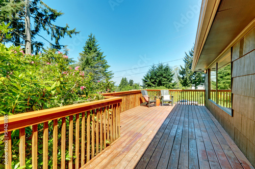Fotografia  Long Deck, terrace with wood railings and green landscape.