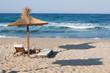Wooden chairs under an umbrella on sand beach