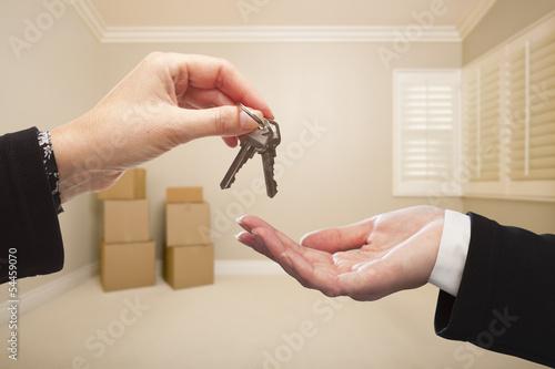 Fotografie, Obraz  Woman Handing Over the House Keys Inside Empty Tan Room