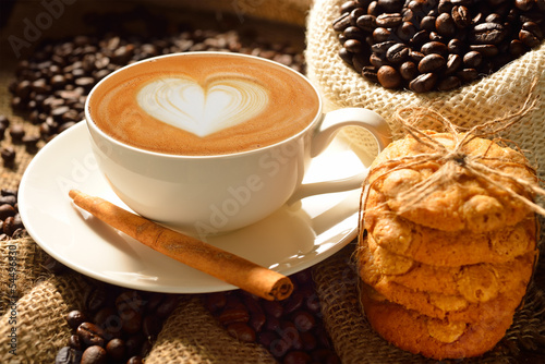 A cup of cafe latte with coffee beans and cookies