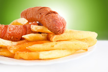 Fried Sausage With French Fries Served On White Plate