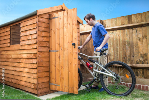 Fotografía Man pushing his bike into a shed for storage