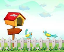 A Bird House With An Arrow Board And Birds Above The Fence