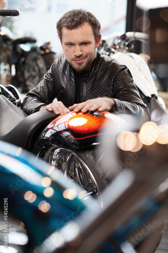 Customer examining motorcycle. Cheerful young men in leather clo