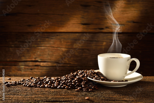 Fotografia  Coffee cup and coffee beans on old wooden background