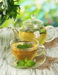 Fototapeta Do herbaciarni Teapot and cup of herbal tea with fresh mint flowers