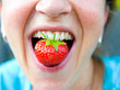 canvas print picture - woman is eating a strawberry