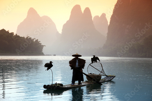 Tuinposter Guilin YANGSHUO - JUNE 18: Chinese man fishing with cormorants birds in