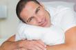 Attractive man hugging his pillow