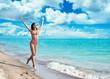 Happy young woman in bikini running on the beach