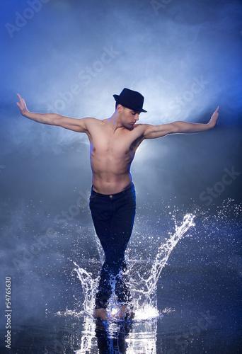 aa4b5c546 Wet dancer. Young male dancer in black fedora dancing on the wet ...