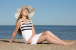 beautiful woman in white dress and hat sitting on the beach