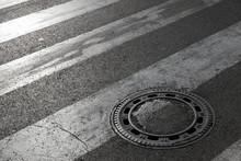Sewer Manhole Cover On Asphalt Road