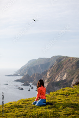 Woman Sitting Relaxed On Coastline Hillside Poster