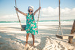 Adorable little girl in a dress and sunglasses on swing on white