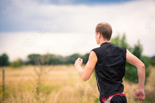 29b6e74bb670 Back of sportive young man jogging outdoor - Buy this stock photo ...