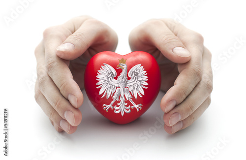 Fotografía  Hands covering Polish coat of arms on a red heart