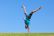 Outdoor portrait of a cute teenage black boy jumping over a blue