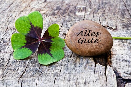 Obraz na plátně  vierblättriges Kleeblatt mit Stein auf Holz, Alles Gute