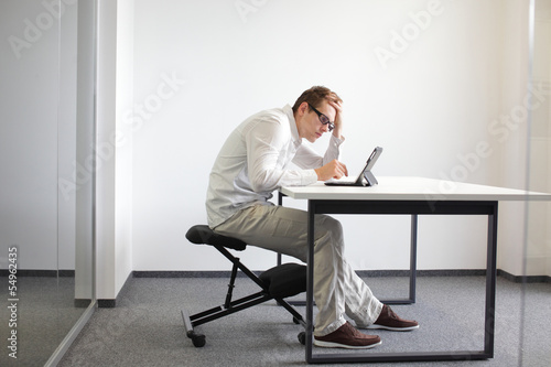 Fotografie, Obraz  bad sitting posture at workstation. man on kneeling chair