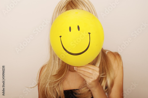 Photo  Girl holding smiley face balloon in front of her