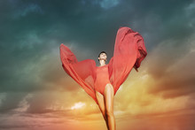 Beautiful Woman With Red Chiffon In Front Of Cloud Background