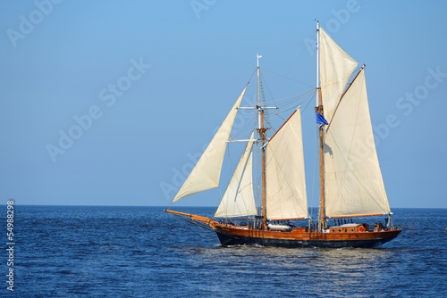 Keuken foto achterwand Schip old historical tall ship (yacht) with white sails in blue sea