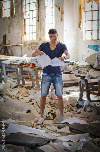 Photo Stands Stairs Attractive young man in messy office or working place