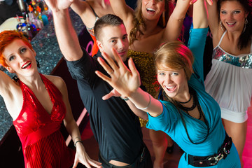 Young people dancing in club or disco, men and women
