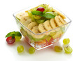 Tasty fruit salad in glass bowl, isolated on white