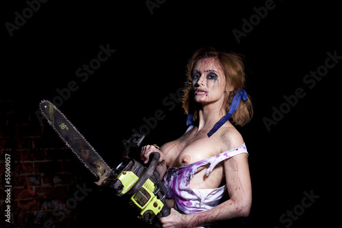Fotografie, Obraz  Horrific madwoman on a dark background and chainesaw