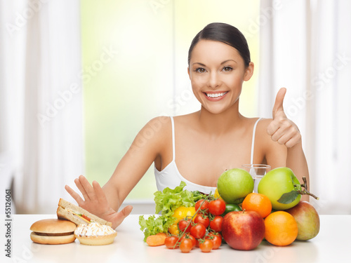 woman with fruits rejecting junk food Poster