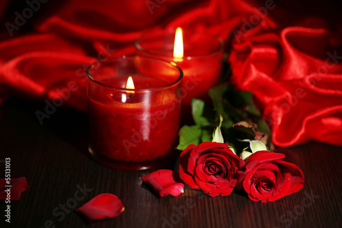 Beautiful romantic red candle with flowers and silk cloth,
