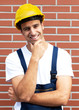 Friendly smiling worker in front of a brick wall