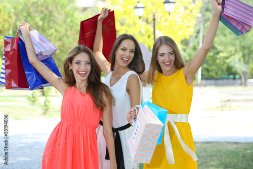 Keuken foto achterwand Carnaval Three beautiful young woman with shopping bags in park