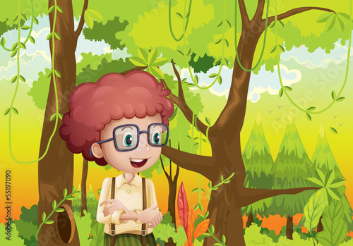 A curly boy in the forest near the trees #55197090