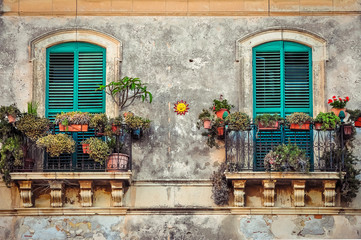 Fototapeta Beautiful vintage balcony with colorful flowers and doors