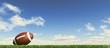 Leinwandbild Motiv American football ball, on the grass, with fluffy couds sky in t