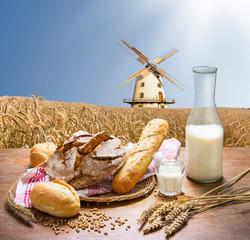 Obraz na Szkle Do restauracji frische Backwaren vor einem Getreidefeld mit Windmühle