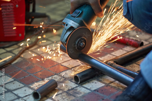 Male hand cuts off pieces of water pipe with angle grinder Fotobehang