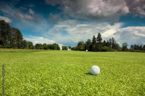 Spoed Foto op Canvas Golf Golf ball on the course, green grass, blue sky and white clouds
